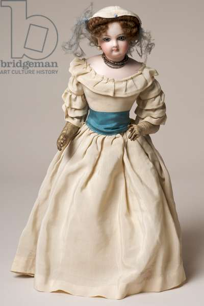 Bisque fashion doll with swivel head, wearing a long cream dress and hat (ceramic & textile)