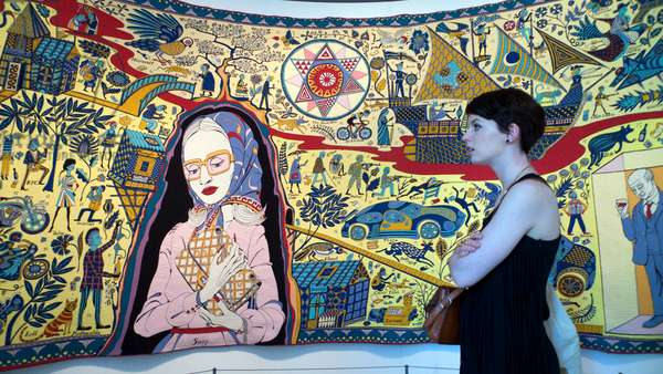 A young woman looking at the the Walthamstow Tapestry