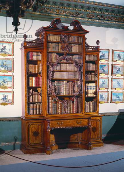 Glass-fronted bookcase with large central case decorated with an elaborately carved inner frame incorporating a carved violin, flanked by two shorter narrow cases resting on a lower section of two side cupboards and a central reading bay