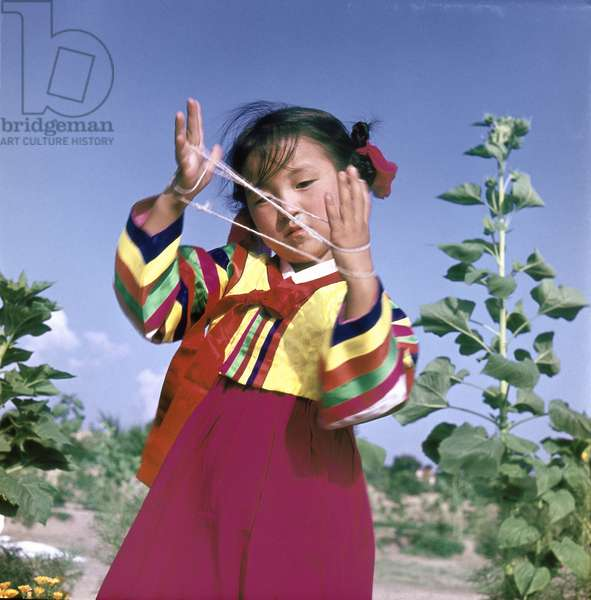 A young Korean girl in traditional dress playing Cat's Cradle