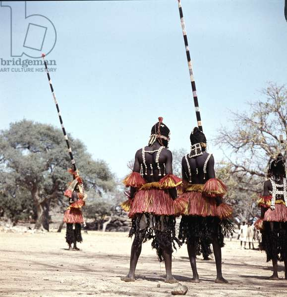 Dogon masqueraders perform in a ceremony known as a dama, which draws the souls of honoured dead away from the village and brings prestige to their families