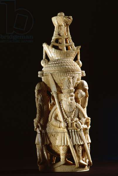 An ivory salt cellar around the base of which are figures of Portuguese noblemen