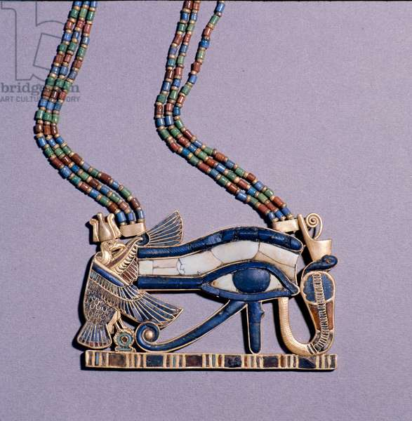 A pendant from the tomb of Tutankhamun in the form of a 'Wedjat eye', symbol of protection, flanked by the vulture goddess, Nekhbet and the snake goddess Wadjet, protectors of Upper & Lower Egypt