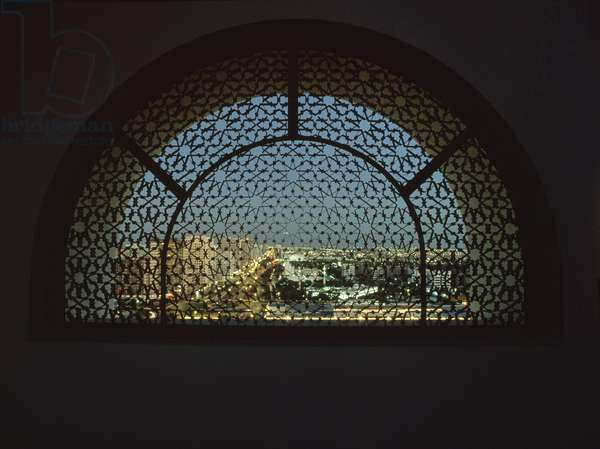 View of the city of Abu Dhabi at night through the ornate Islamic-inspired metal grill on the roof of a tower