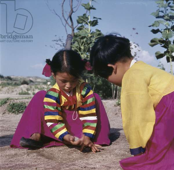 Two young Korean girls in brightly coloured national dress, crouching on the ground as they play a game with small stones