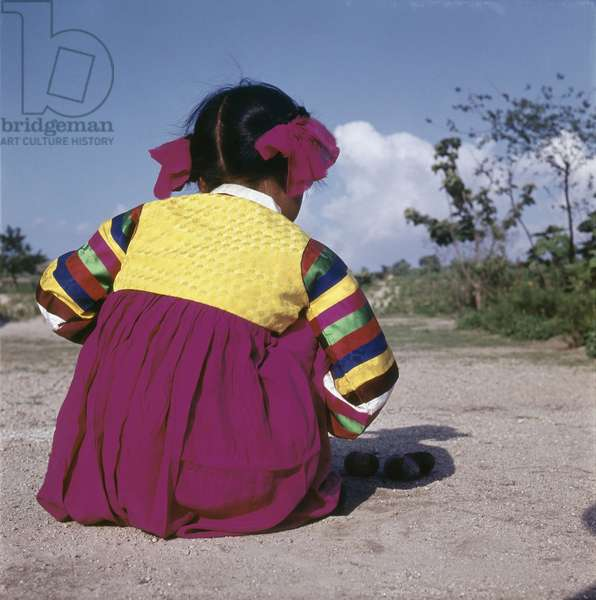 A young Korean girl in brightly coloured national dress, crouching on the ground as she plays a game