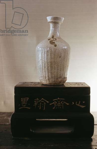 A vase with a white glaze, serrated body and small flower motif painted in black
