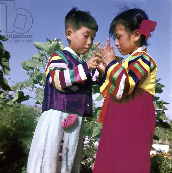 Two young Korean children in traditional dress playing Cat's Cradle