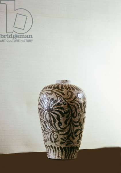 A vase decorated with a stylized pattern of leaves and flowers