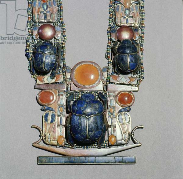 A scarab pectoral from the tomb of Tutankhamun with straps formed from inlaid plaques with uraei (cobras), scarabs & solar discs