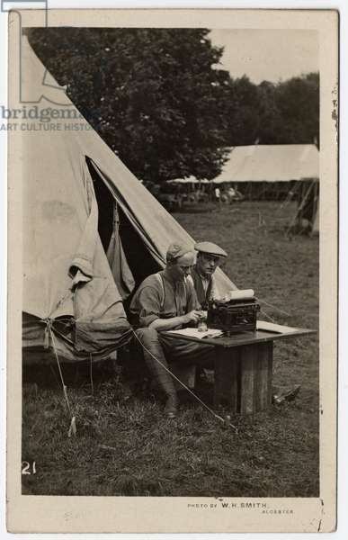 Two men sitting outside a tent with a typewriter on a table before them. Ragley Park. Circa 1915