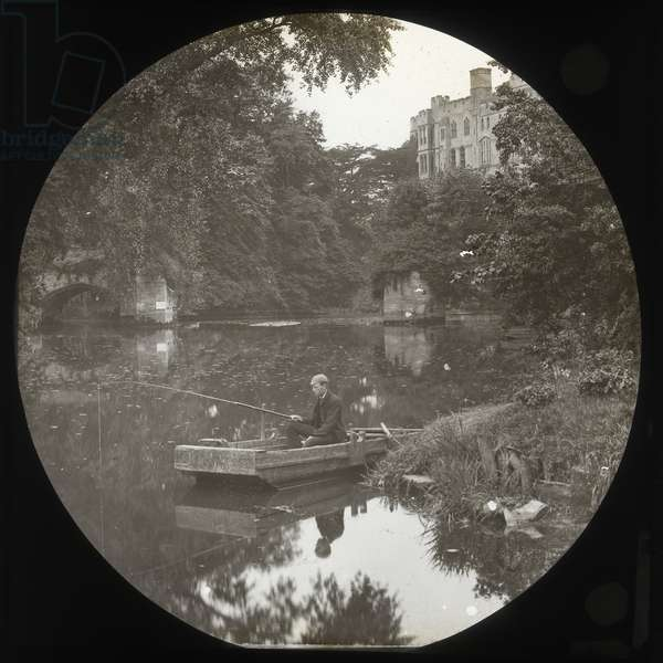 Young man fishing from a punt on the River Avon, Warwick Castle, c.1890 (b/w photo)
