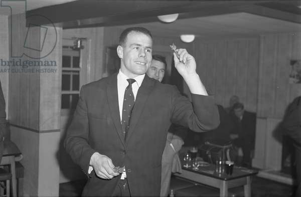 Coventry City Football Club players pictured at a get together at the Weavers Arms, Wood End, near Fillongley. Wednesday 27 January 1965. City skipper George Curtis about to throw a dart.