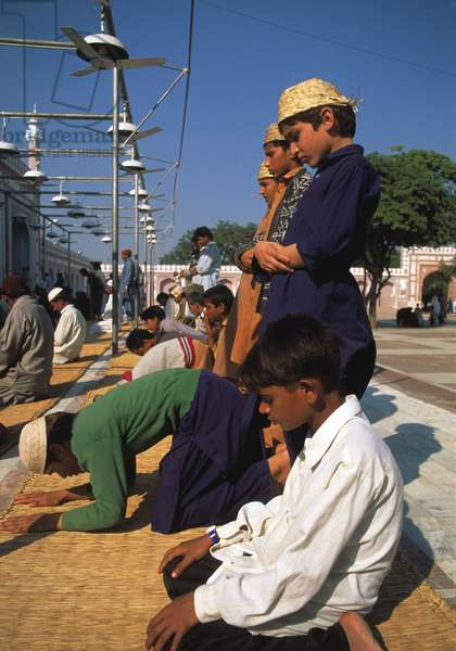 Young boys offering prayer in a mosque, showing several prayer positions (photo)