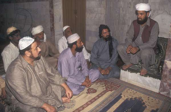 Imam of a small mosque talking to the congregation (photo)