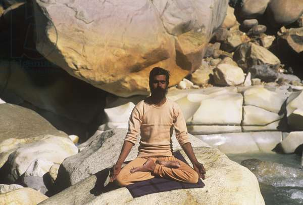 A swami practising yoga by the Ganges (photo)