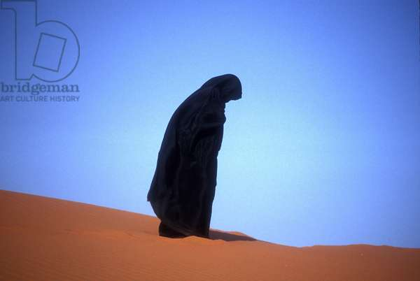 Muslim woman praying on a sand dune (photo)