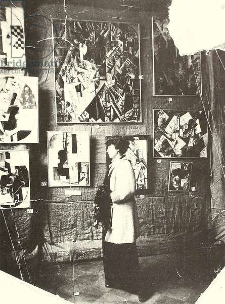 Alexandra Ekster in front of Udaltsova's paintings at the exhibition The Store, Moscow, 1916 (b/w photo)