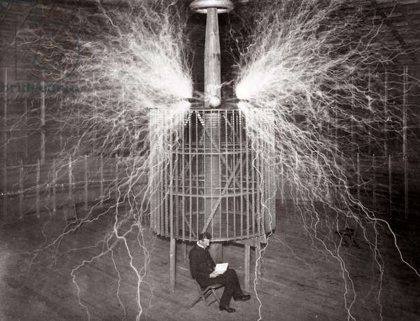 "Nikola Tesla sitting in his Colorado Springs laboratory with his ""Magnifying Transmitter"""
