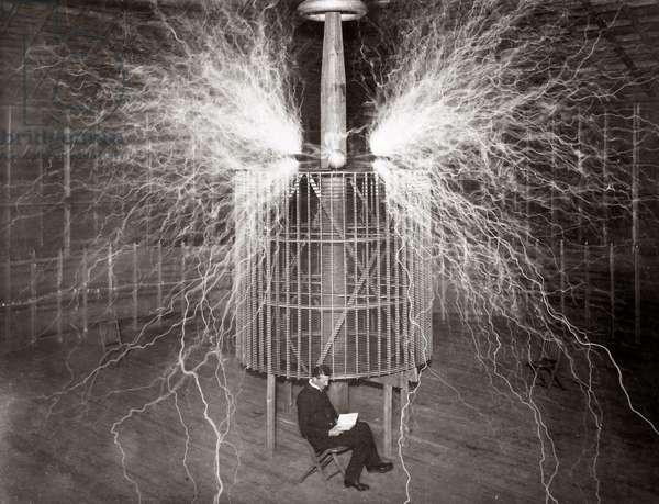 "Nikola Tesla sitting in his Colorado Springs laboratory with his ""Magnifying Transmitter"""