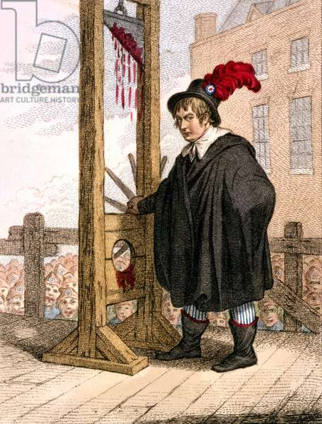 George Tierney dressed as an executioner standing next to a guillotine.