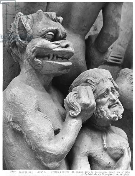 Devil pushing a damned person in the fire, from the Last Judgement of the Cathedral of St. Etienne in Bourges (detail) (plaster cast from stone) (b/w photo)