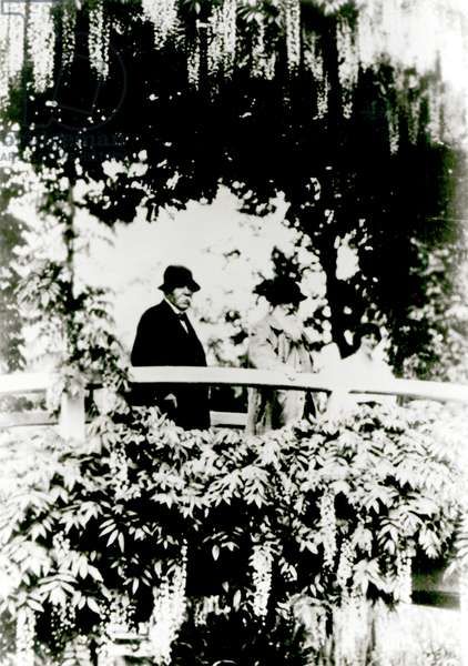 Georges Clemenceau (1841-1929) Claude Monet (1841-1926) and Alice Butler (1894-1949) on the Japanese Bridge in Monet's garden, Giverny, 1921 (b/w photo)