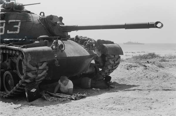 American soldier reads a newspaper in the shade under a U.S. Marine tank in Beirut, Lebanon, 1958 (b/w photo)