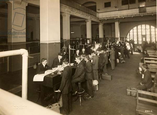 Immigrants being registered in the Main Hall, U. S. Immigration Station, 1902-10 (b/w photo)