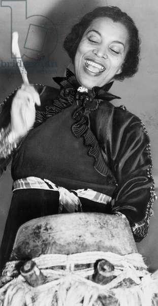 Zora Hurston beating the hountar, or mama drum. 1937 (photo)