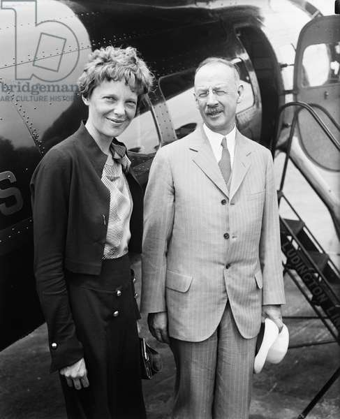 Amelia Earhart (L), Portrait with Man in front of Airplane, 1932 (b/w photo)