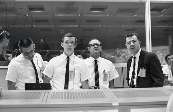 Standing at the flight director's console, viewing the Gemini-10 flight display in the Mission Control Center, are (left to right) William C. Schneider, Mission Director; Glynn Lunney, Prime Flight Director; Christopher C. Kraft Jr., MSC Director of Flight Operations; and Charles W. Mathews, Manager, Gemini Program Office, 18th July 1966 (b/w photo)