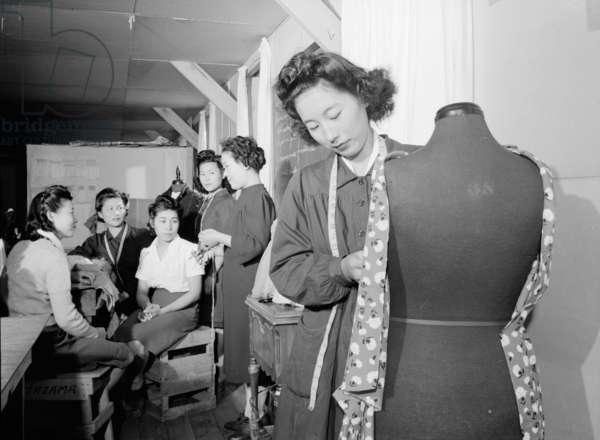 Mrs. Ryie Yoshizawa teaching a dressmaking class to women students at Manzanar, 1943 (b/w photo)