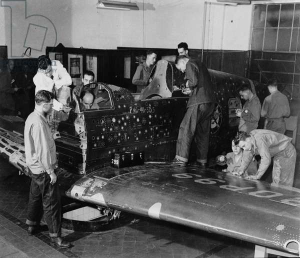"Soldier trainees work on ""Flying Patch,"" a Currtiss ""Warhawk"" fighter plane without engine or tail assembly, with simulated bullet holes and patches, c.1942 (b/w photo)"