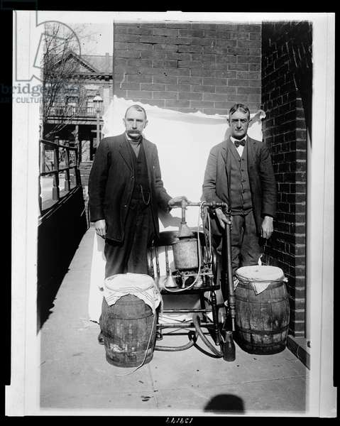 Two men posing with a whiskey still, 1920-30 (b/w photo)