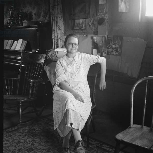 Mrs. Hull in one room basement dugout home at Dead Ox Flat, 1939 (b/w photo)