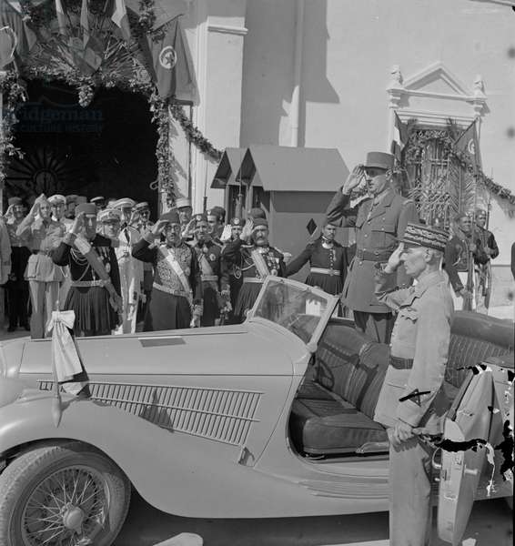 General Charles de Gaulle, Accompanied by General Charles Mast, Saluting as Band Plays Marseillaise Outside Summer Palace of Bey of Tunis, Carthage, Tunisia, Marjorie Collins for Office of War Information, June 1943 (b/w photo)