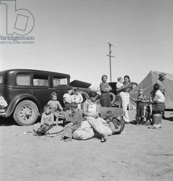 Migrating families camp by the road on their way to California, 1937 (b/w photo)