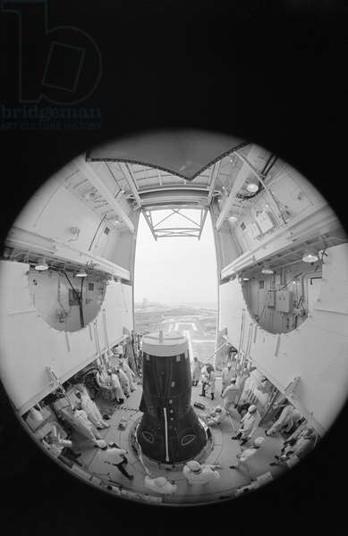 Fisheye camera lens view of activity in white room atop Pad 19 as technicians secure equipment in preparation for erector lowering. Inside the Gemini-10 spacecraft are astronauts John W. Young, command pilot, and Michael Collins, pilot, 18th July 1966 (b/w photo)