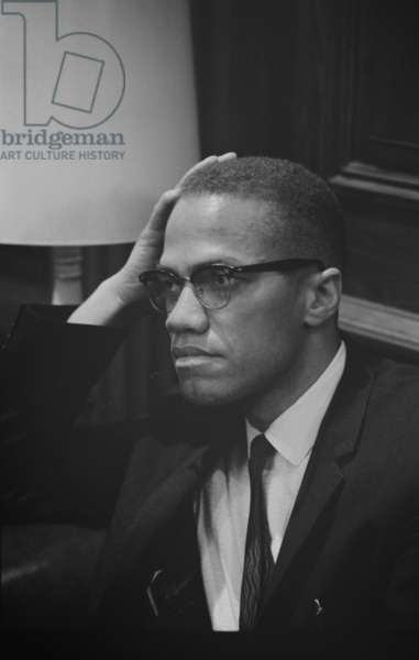 Malcolm X waits at Martin Luther King press conference, 1964 (b/w photo)