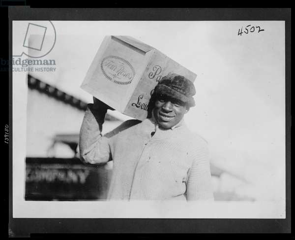 """African American man carrying a case of """"Four Roses"""" whiskey on his shoulder, possibly confiscated by the U.S. Internal Revenue Bureau, 1921-32 (b/w photo)"""