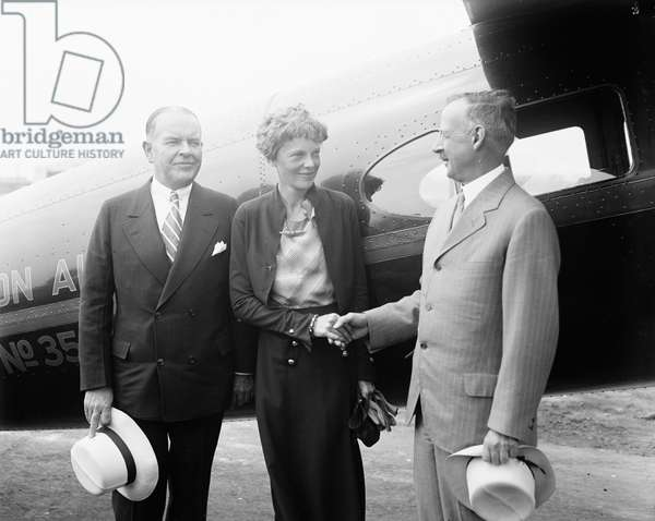 Amelia Earhart, Center, Portrait Shaking Hands with Man in front of Airplane, 1932 (b/w photo)