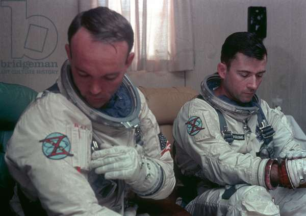 Astronauts John W. Young (right), command pilot, and Michael Collins (left), pilot, prime crew for the Gemini-10 spaceflight, undergo suiting up operations in the Launch Complex 16 suiting trailer, 18th July 1966 (photo)