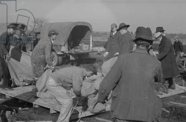 Setting up a tent in the camp for white flood refugees at Forrest City, Arkansas, 1937 (b/w photo)