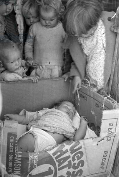 Baby in a cardboard box crib at a Californian migrant camp pre-school, 1936 (b/w photo)