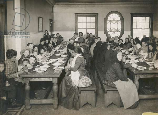 Immigrants served a free meal at Ellis Island, c.1906 (b/w photo)