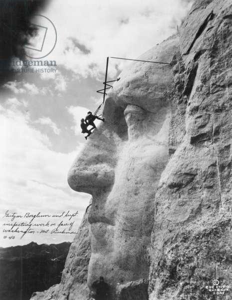 Gutzon Borglum  inspecting work on Washington at Mount Rushmore, 1932 (b/w photo)