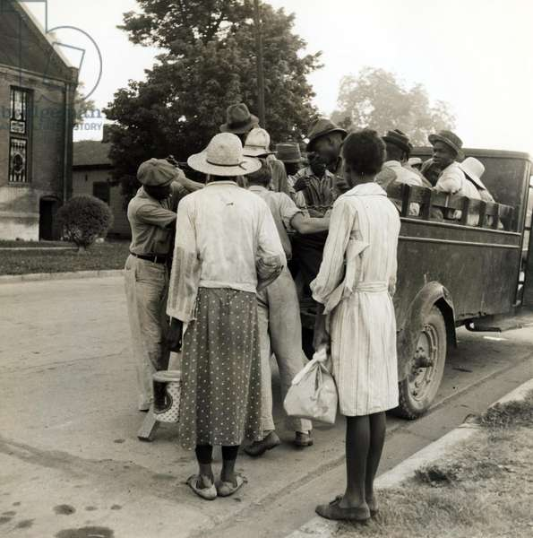 Cotton day workers board a truck in Mississippi, 1937 (b/w photo)