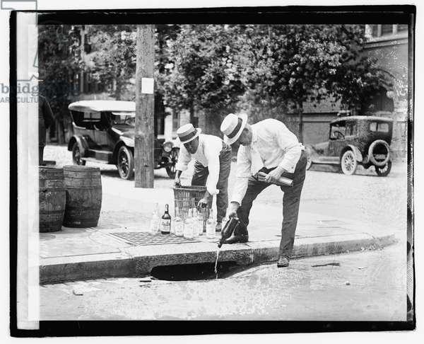 Two men pouring liquor into storm drain, 8 July 1921 (b/w photo)
