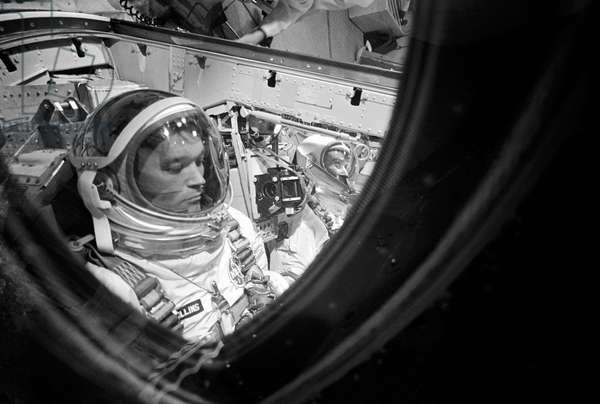 Close-up of astronaut Michael Collins, Gemini-10 pilot, making final adjustments and checks in the Gemini spacecraft during prelaunch countdown, 18th July 1966 (b/w photo)